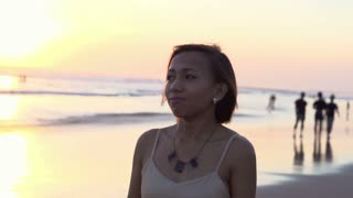 Young, pensive woman walking on the beach during sunset, super slow motion, shot at 240fps