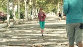Young people greeting each other while jogging on park, slow motion shot at 120fps