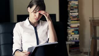 Young, pretty businesswoman having headache during work at home