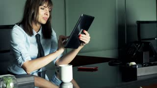 Young, pretty businesswoman working with tablet computer in the office
