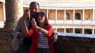 Young, pretty couple taking photo with cellphone while sightseeing old, amphitheatre building