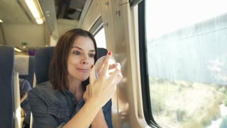 Young pretty woman applying lipstick on her lips in the train