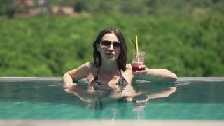 Young pretty woman drinking cocktail on swimming pool