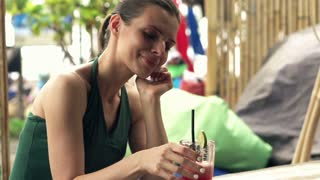 Young, pretty woman drinking cocktail sitting in bar close to the beach, super slow motion, shot at 240fps