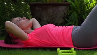 Young, pretty woman exercising sit-ups in the garden 240fps