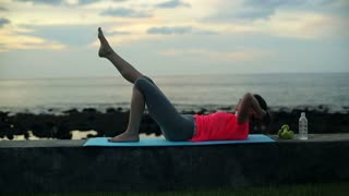 young, pretty woman exercising sit-ups on the wall by the sea