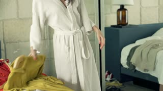 Young, pretty woman in bathrobe trying dresses in front of the mirror in bedroom