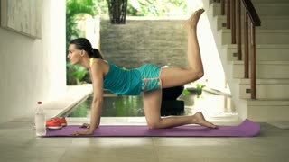 Young, pretty woman lifting legs on mat in luxury villa, 4K