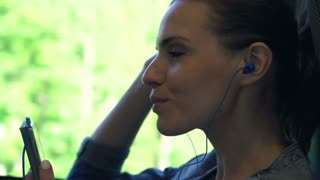 Young, pretty woman listening to music on cellphone on a train, 240fps