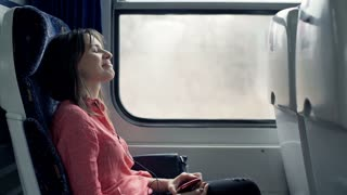 Young, pretty woman listening to music on cellphone sitting on the train