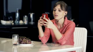 Young, pretty woman listening to music on smartphone by table in the kitchen