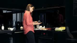 Young, pretty woman preparing sandwich for breakfast in the kitchen