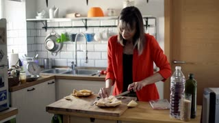 Young, pretty woman preparing sandwich for breakfast on wooden table