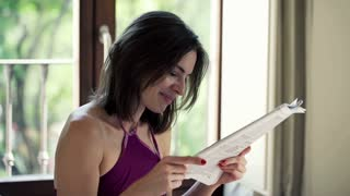 Young, pretty woman reading magazine at home
