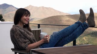 Young pretty woman relaxing and drinking coffee while sitting on terrace with mountains view, 4K