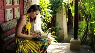 Young pretty woman sitting with laptop on bench in front of country house