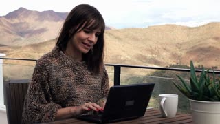 Young pretty woman sitting with laptop on terrace with mountains view, 4K