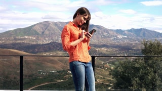 Young pretty woman standing with smartphone on terrace with mountains view, 4K