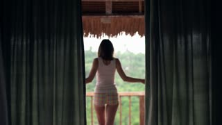 Young, pretty woman stretching arms and enjoying view on the terrace in the country house, 240fps