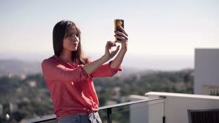 Young, pretty woman taking selfie photo standing on terrace with beautiful view