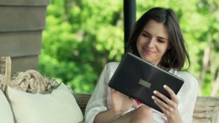 Young, pretty woman using tablet computer on sofa on terrace