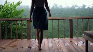 Young, pretty woman walking out on terrace and stretching her arms, slow motion shot at 240fps