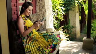 Young pretty woman working with smartphone on bench in front of country house
