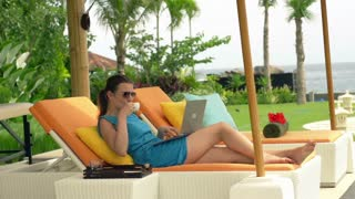 Young, pretty woman working with laptop on sunbed in luxury garden