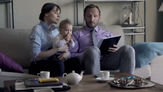 Young sad business couple with child sitting over documents on sofa at home