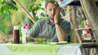 Young sad man eating satay chicken in cafe outdoor restaurant with exotic garden in Thailand