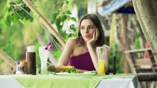 Young sad woman sitting in outdoor restaurant with exotic garden in Thailand