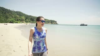 Young sportive woman walking along on the beach, super slow motion 240fps