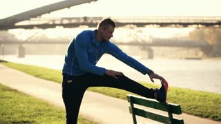 Young sporty man stretching legs on the bench in city