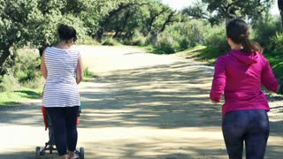 Young, sporty woman jogging in the park, mother with baby stroller walk past