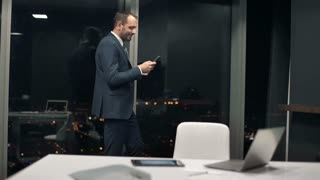 Young, successful businessman taking selfie photo with cellphone standing by window in the office