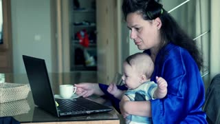 Young, tired mother in bathrobe trying work on laptop with her little child