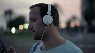 Young trendy man listening to music on smartphone in the evening