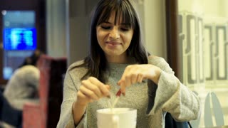 Young woman adding sugar into coffee and mixing sitting in cafe