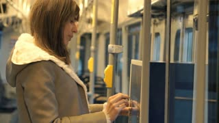 Young woman buying ticket from vending machine on the tram