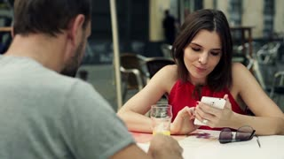 Young woman checking something on smartphone while sitting with her boyfriend in cafe