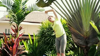 Young woman doing bend exercise in the garden