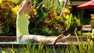 Young woman doing legs stretching in the garden