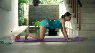 Young woman doing plank exercise on mat n luxury villa, 4K