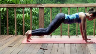 Young woman doing plank exercise on terrace with tropical view