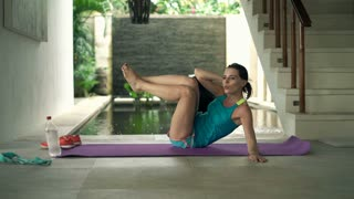 Young woman doing twist sit-ups on mat in luxury villa, 4K