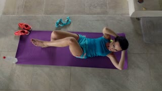 Young woman doing twist sit-ups on mat in luxury villa, top view, 240fps