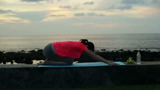 young woman doing yoga pose on the wall by the sea