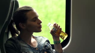 Young woman drinking apple juice while sitting on a train shot at 240fps