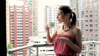 young woman drinking coffee on the balcony and enjoining city view
