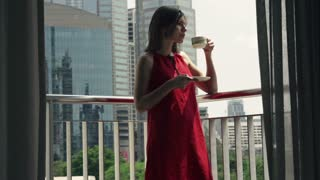 Young woman drinking coffee on the terrace in the city, shot at 240fps